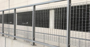 A parking garage with aluminum bar grating panels installed in front of it for protection