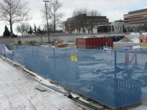 Temporary fence installed around a construction site with blue transparent windscreen and yellow caution signs