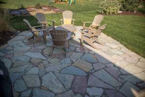 Stone patio with a circle of lounging chairs seated around a round table in a backyard